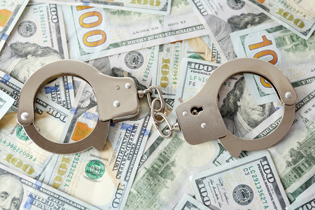 Menottes sur les billets en dollars. Concept de corruption