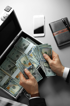 Businessman with tablet and notebook counting money
