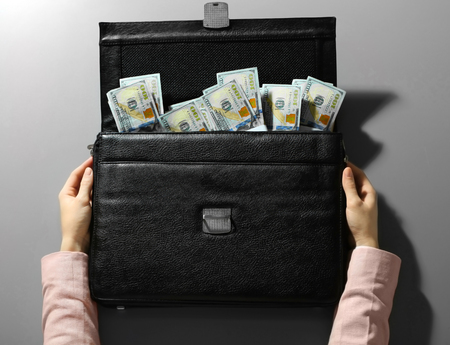 Businesswoman and brief case with money