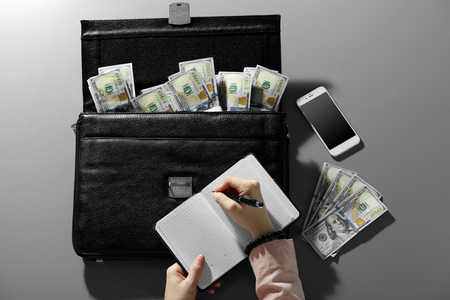 Businessman writing in notebook on brief case full of money 스톡 콘텐츠