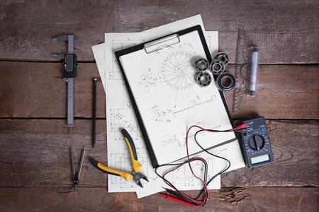 Digital multimeter and blueprints on a wooden background.