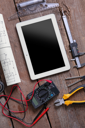 Digital multimeter and tablet on a wooden background.