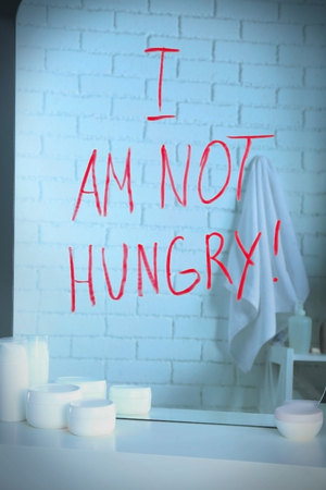 Text I AM NOT HUNGRY written on mirror in the bathroom