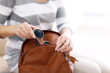 Young woman packing her brown leather backpack.