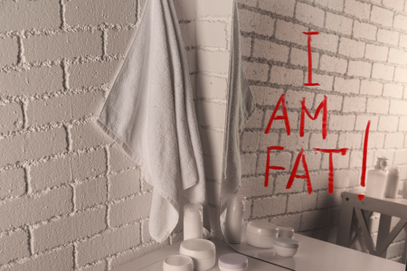 Text I AM FAT written on mirror in the bathroom Stock Photo