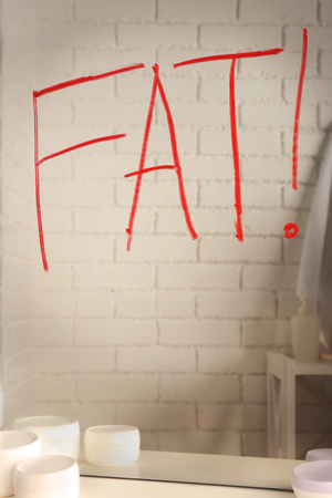 Word FAT written on mirror in the bathroom