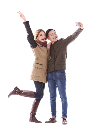 Young couple taking selfie in their winter clothes isolated on white