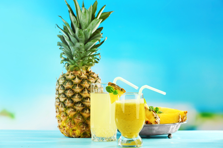 Pineapple juice and smoothie in cocktail glasses on blue blurred background