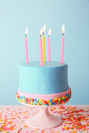 Birthday cake with candles on turquoise  background.