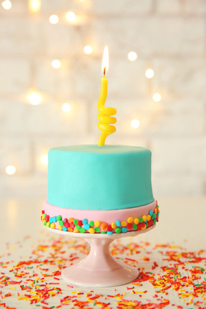 Birthday cake with one candle on white   background.