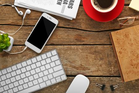 Posto di lavoro con telefono cellulare, periferiche e giornali sulla tavola di legno