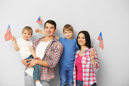 Parents and their sons with  American flags on the light blue wall Stok Fotoğraf