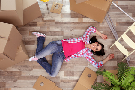 Young woman moving in new house. Top view. Stock Photo
