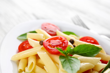 Plate of pasta with cherry tomatoes and basil leaves on table closeup