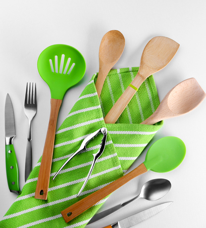 Set of kitchen tools with green napkin, isolated on white Stock Photo