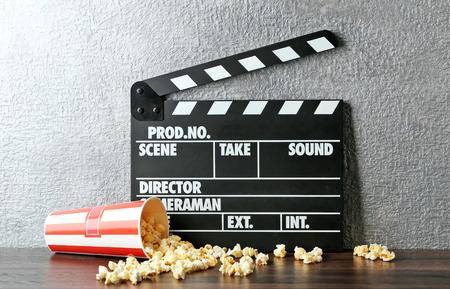 Movie clapper and popcorn against grey wall background Foto de archivo