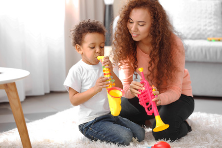 Little boy and a young girl playing  with musical toys on the floor