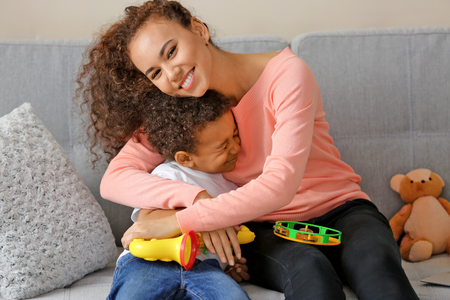 Young woman and little boy having fun in a living room Banque d'images