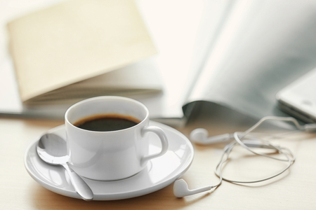 White cup of the coffee and a phone on the table.