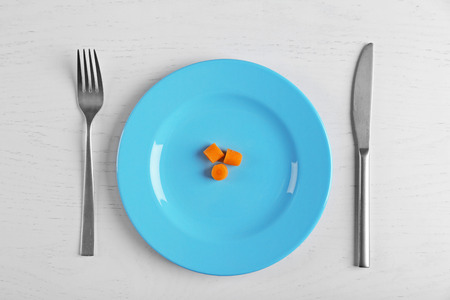 Slices of baby carrots in a blue plate on white table.. Top view. Stock Photo