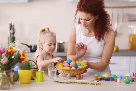 Mother and daughter decorating Easter eggs in the kitchen Reklamní fotografie