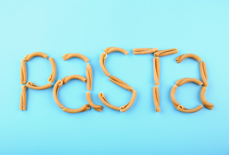 Pasta word made of casarecce on turquoise background Stock Photo