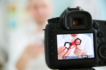 Young male blogger with tie bow on camera screen Stock Photo