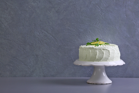 Big lime cake on a white stand beside grey wall