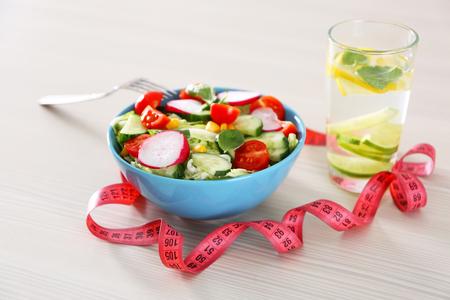 Fresh vegetarian salad and glass of lemonade on wooden table closeup