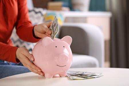 Female hand putting money into piggy bank closeup 写真素材
