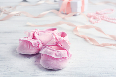 Beautiful composition with baby booties on wooden background