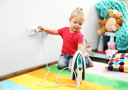 Klein meisje speelt met ijzer in de kinderkamer Stockfoto