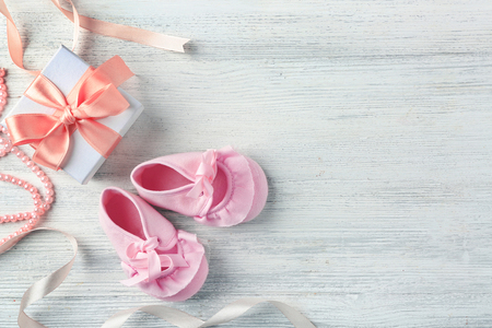 Beautiful composition with baby booties and gift box on wooden background 免版税图像