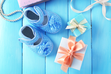 Beautiful composition with baby booties and gift box on wooden background Zdjęcie Seryjne
