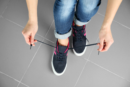 Woman tying up lace on sport shoes