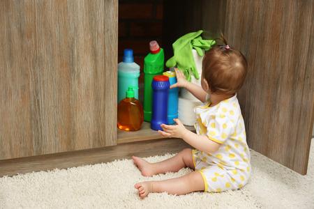 Niña jugando con detergentes en la cocina Foto de archivo
