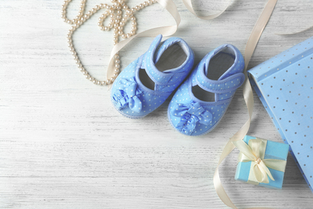 Beautiful composition with baby booties and gift box on wooden background Reklamní fotografie