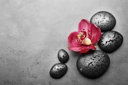 Spa stones and red orchid on grey background Stock Photo