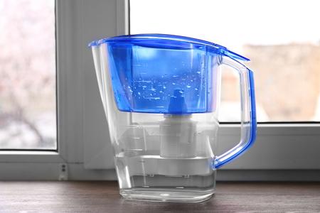 Water filter jug on the wooden windowsill