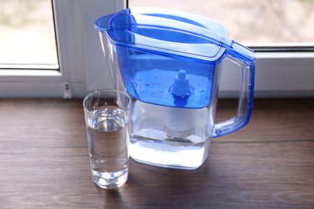 Dzbanek z filtrem do wody i szklanka na drewnianym parapecie