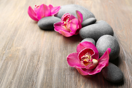 Stones and red orchid on wooden background