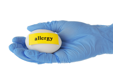 Allergic food concept. Hand in glove holding egg isolated on white
