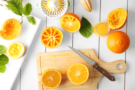 Juicing delicious oranges on white wooden table Stock Photo