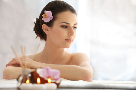 Young woman with flower relaxing in spa center
