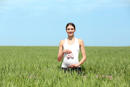 Pregnant woman holding babys bootees in field