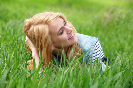 Young beautiful woman on green grass 写真素材