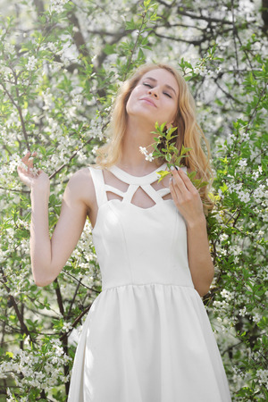 Young beautiful woman on blooming tree background 写真素材