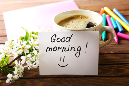 Cup of fresh coffee and note on wooden background