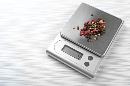Mix of peppers with digital kitchen scales on wooden background