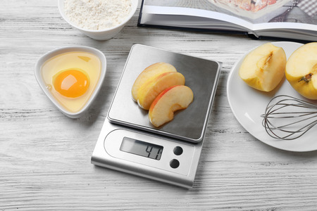 Making apple pie. Using digital kitchen scales on wooden table. Cooking apple cake concept Stock fotó